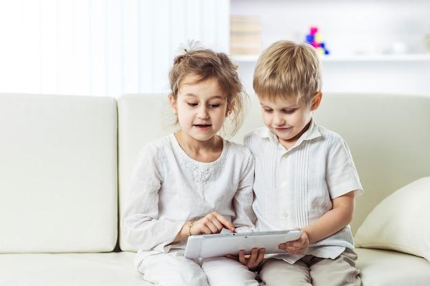 デジタルタブレットを持った小さな子供たち。教育とテクノロジー。子供向けの教育用コンピュータゲーム。