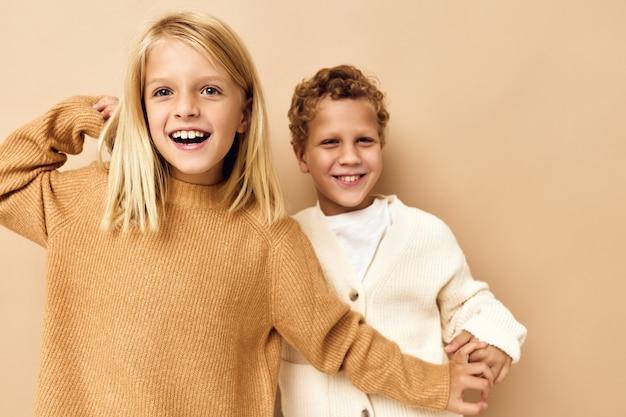 薄茶色の髪のベージュの背景を持つ小さな子供たち