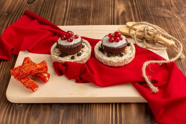 クランベリーとクリーム色の木製の机の上のクラッカーと小さなチョコレートケーキ
