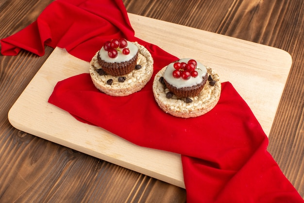 Little chocolate cakes with cranberries and crackers on cream wooden desk