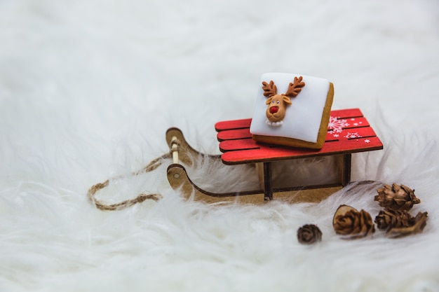 Little christmas cookie on a small wooden sledge on lights . merry christmas, poster or postcard .