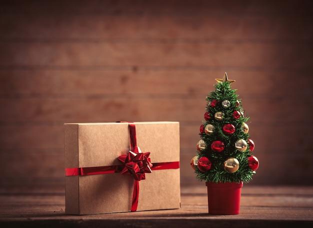 木製のテーブルと背景に小さなクリスマスツリーとギフトボックス