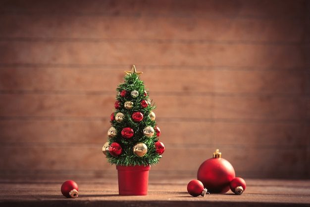 Little christmas tree and baubles on wooden table and background
