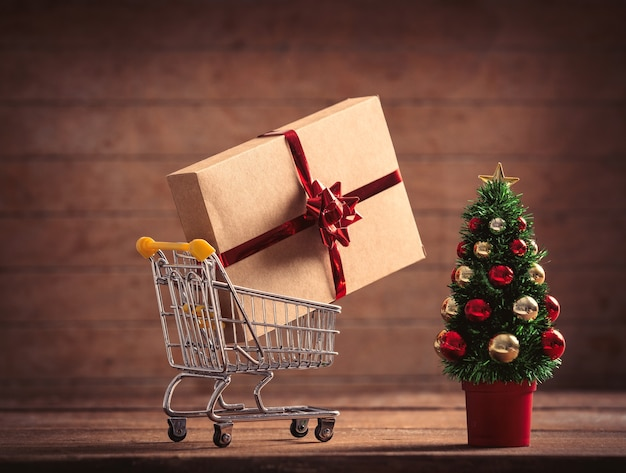 Little christmas tree and gift box in supermarket cart on wooden table and background