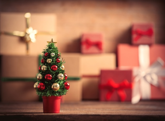 Little christmas tree and gift boxes on background