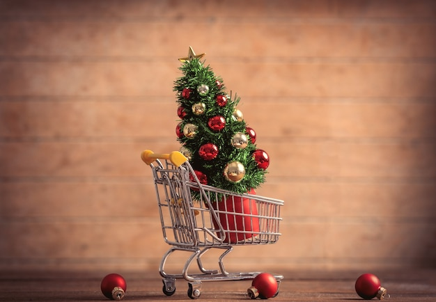 Little christmas tree in supermarket cart on wooden table and background
