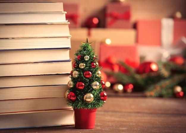 Маленькая рождественская елка с книгами и подарочными коробками на фоне