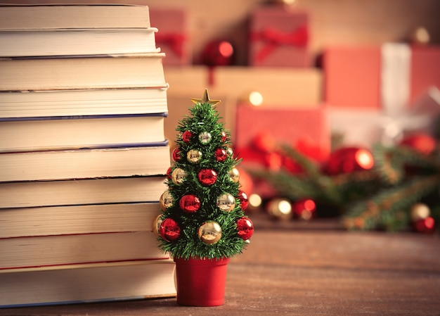 Little christmas tree with books and gift boxes on background