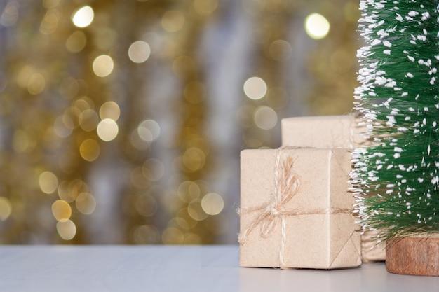 木製のテーブル、黄金のボケ味、コピー領域のギフトボックスと小さなクリスマスツリー。