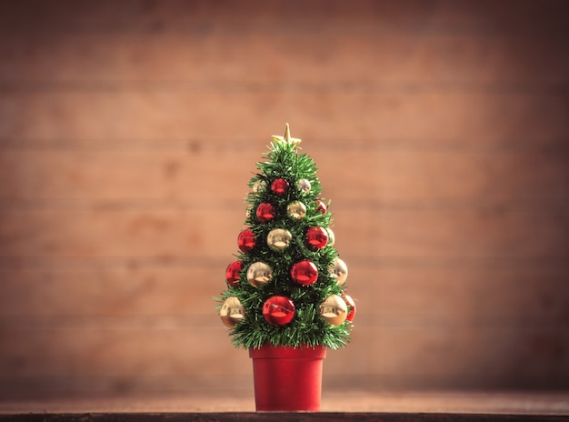 Little christmas tree on wooden table and background