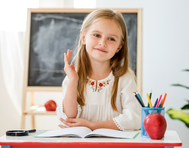 Little clever blond girl raise a hand for the answer sitting at the white desk on the background of blackboard in the school class