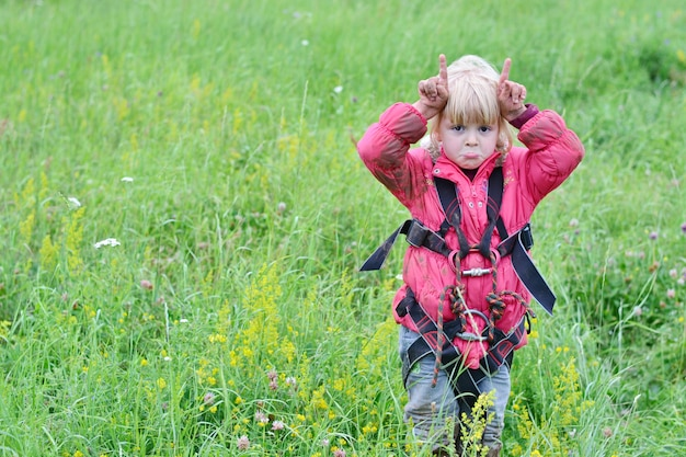 Little climber girl in a red jacket in nature