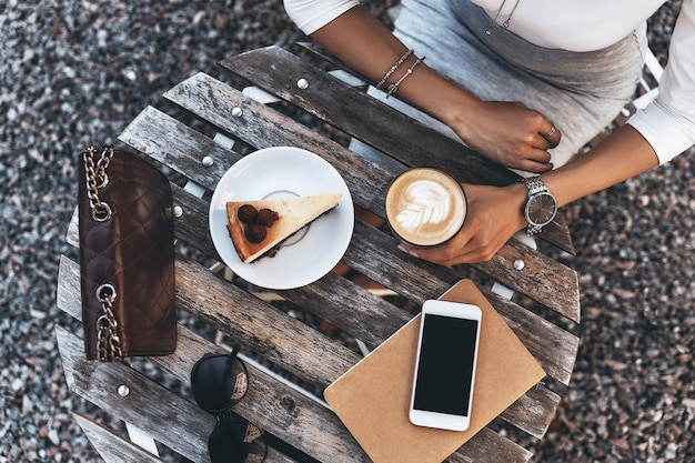 Little coffee break. close-up top view of young woman holding a cup of coffee while sitting in restaurant outdoors