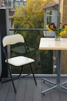 Little coffee table with vase flowers and one chair at cafe on balcony with houses