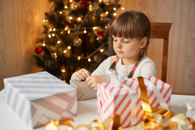 テーブルに座ってクリスマスボックスを梱包する2つのピグテールを持つ小さな集中した女性の子供