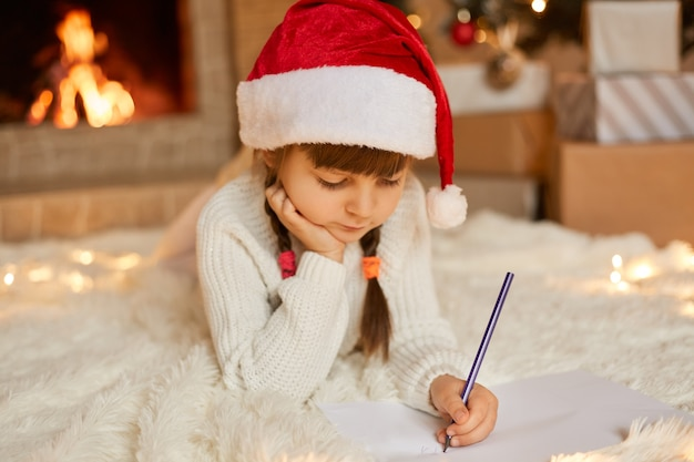 Little concentrated girl wearing white jumper and re santa hat posing on floor while drawing