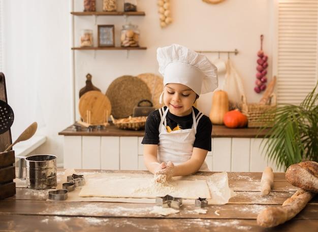 하얀 앞치마와 모자를 쓴 작은 요리사가 부엌의 테이블에서 장소를 반죽합니다.