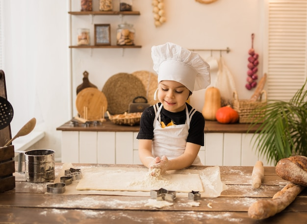 Little cook in a white apron and cap kneads a place at the table in the kitchen