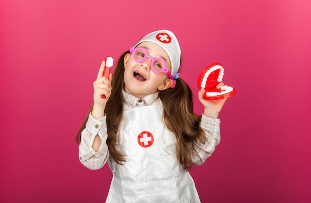 Маленькая крутая девушка-стоматолог-врач в медицинском костюме