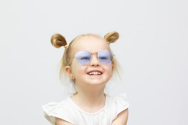 Маленькая крутая улыбающаяся девочка в солнцезащитных очках на белом фоне