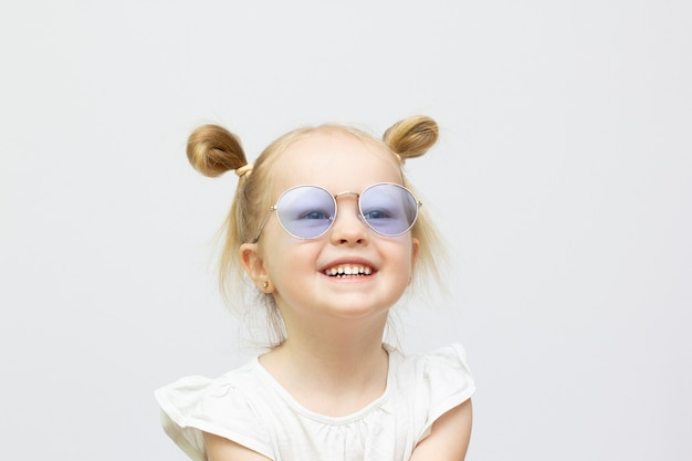 Little cool smilly girl in sunglasses isolated on white background