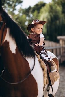 Маленький ковбой, сидящий на лошади
