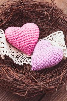 두 개의 크로셰 하트가 있는 작은 아늑한 둥지. 발렌타인 데이 장식