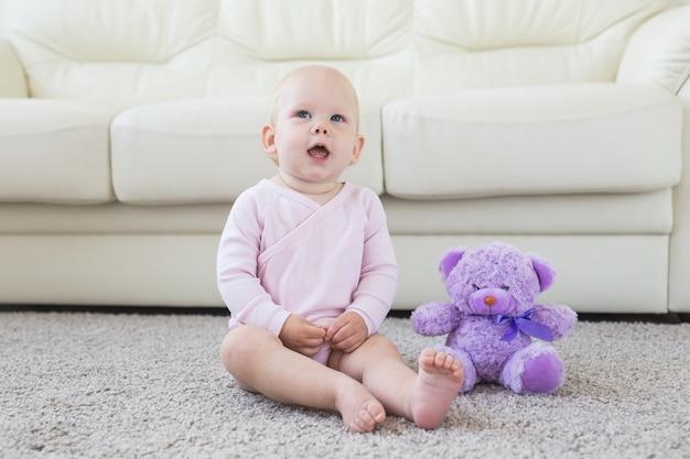 작은 크롤링 아기 소녀 한 살 밝은 빛 거실에서 바닥에 앉아 웃 고