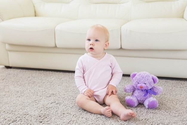 Маленькая ползающая девочка одного года сидит на полу в яркой светлой гостиной, улыбаясь и