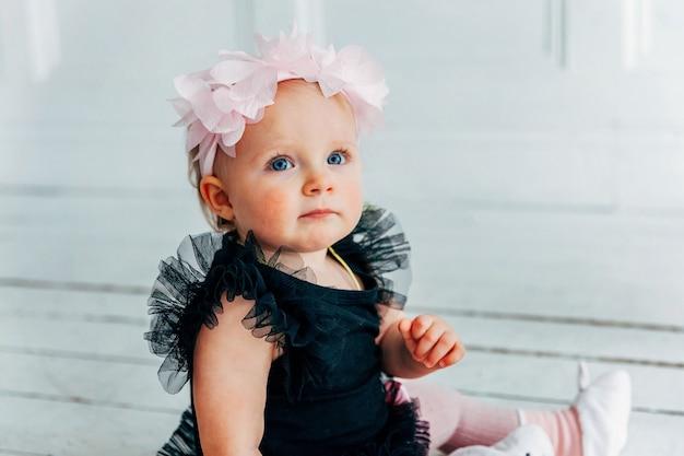 Маленькая ползающая девочка одного года в весеннем венке сидит на полу в яркой светлой гостиной