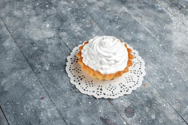 Piccola torta cremosa al forno deliziosa isolata su luce grigia, torta biscotto dolce cuocere