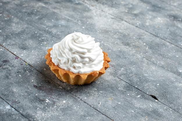 灰色の机の上に隔離されたおいしい焼きたての小さなクリーミーなケーキ、ケーキビスケット甘い砂糖クリーム
