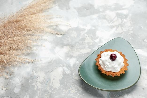 Маленький кремовый торт на тарелке на светлом столе, торт крем фруктовый сладкий бисквит