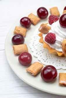 ラズベリーチェリーと小さなビスケットを白く光らせた小さなクリーミーなケーキ、フルーツケーキの甘いベリークリーム