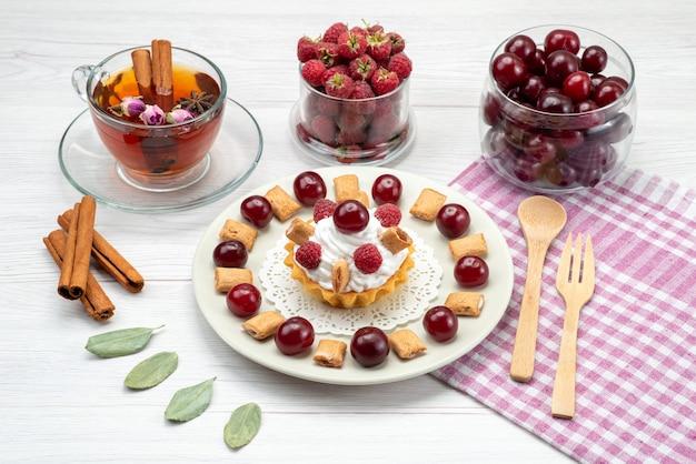 Piccola torta cremosa con lamponi, ciliegie e biscotti piccoli, tè alla cannella sulla scrivania a luce bianca, torta alla frutta, crema ai frutti di bosco