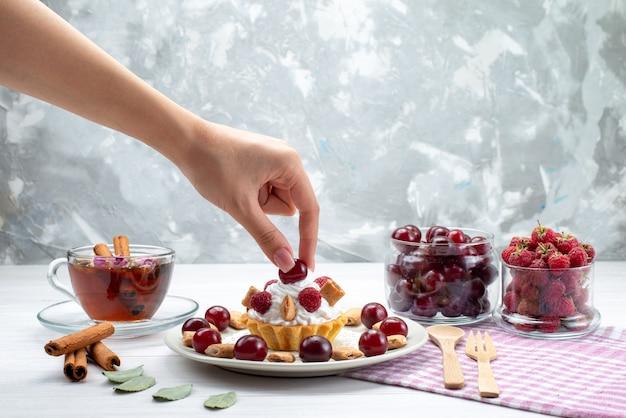 Piccola torta cremosa con lamponi, ciliegie e piccoli biscotti, tè alla cannella su scrivania a luce bianca, crema di frutti di bosco