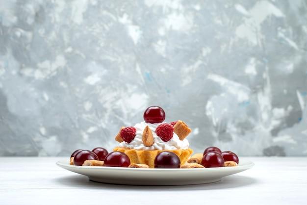 Piccola torta cremosa con lamponi e biscottini sulla scrivania a luce bianca, torta alla frutta con crema di frutti di bosco e ciliegia