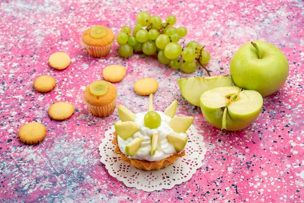 Маленький сливочный торт с нарезанными фруктами, печенье, виноград на цветном столе, торт, сладкая выпечка