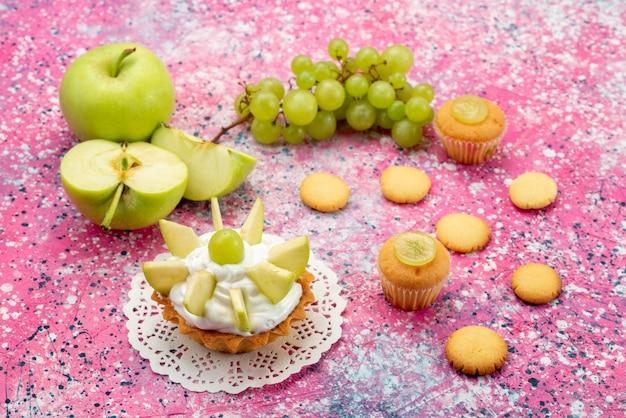 Маленький сливочный торт с нарезанными фруктами, печенье, виноград на цветном столе, торт, сладкий сахарный пирог