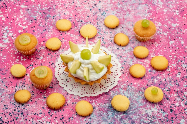 色付きの机の上にスライスしたフルーツクッキー、ケーキシュガーと小さなクリーミーなケーキ