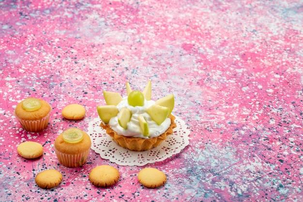 色付きの机の上にスライスしたフルーツクッキーと小さなクリーミーなケーキ、ケーキの甘い砂糖の色