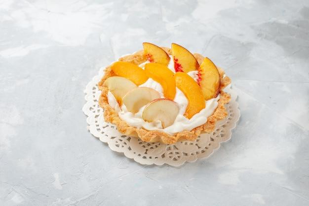 Piccola torta cremosa con frutta a fette e crema bianca su scrivania a luce bianca, torta alla frutta gusto biscotto dolce