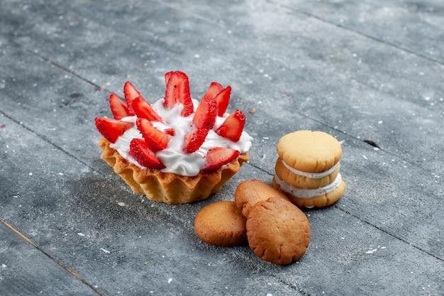 灰色の木製の机の上にクッキーとスライスしたイチゴと小さなクリーミーなケーキ、フルーツベリーケーキ甘い色