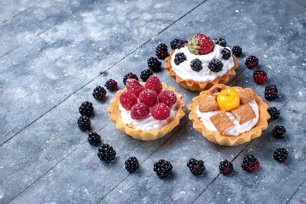 Маленькие кремовые пирожные с малиной вместе с ежевикой в форме сердца на ярком столе, фруктово-ягодный бисквит