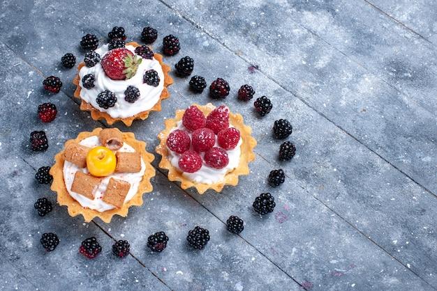 明るい机の上にハート型のブラックベリーと一緒にラズベリーと小さなクリーミーなケーキ、フルーツベリーケーキビスケット