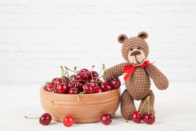 Little crocheted brown bear with cherries on a white background.