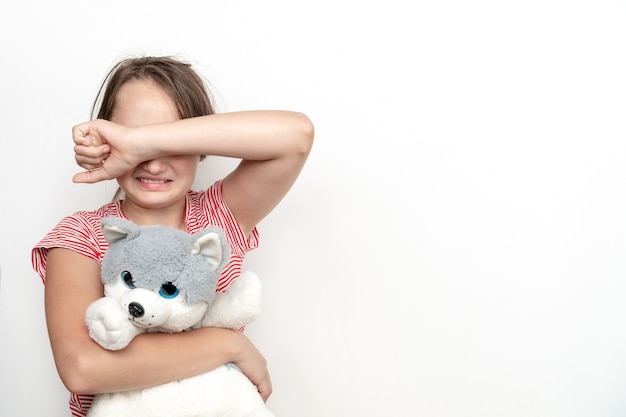 Little crying girl with a toy dog