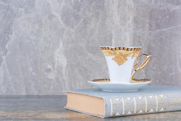 Una piccola tazza in piedi sul libro su sfondo marmo. foto di alta qualità