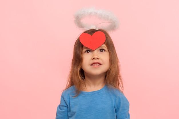 Маленький ангел купидона на день святого валентина. портрет мечтательной очаровательной дошкольной девочки с нимбом, глядя на красную бумажную наклейку в виде сердца на ее лбу. закрытый студийный снимок изолирован на розовом фоне