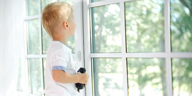 쌍안경으로 창을 보고 있는 호기심 많은 소년